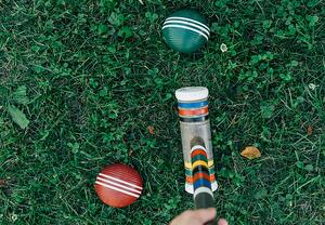 croquet mallet and balls on grass