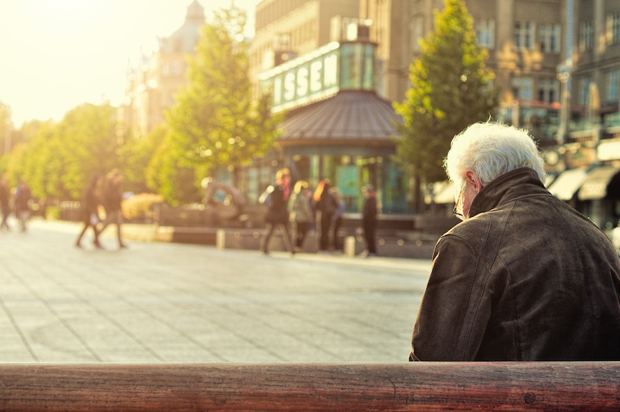 old man on bench in city