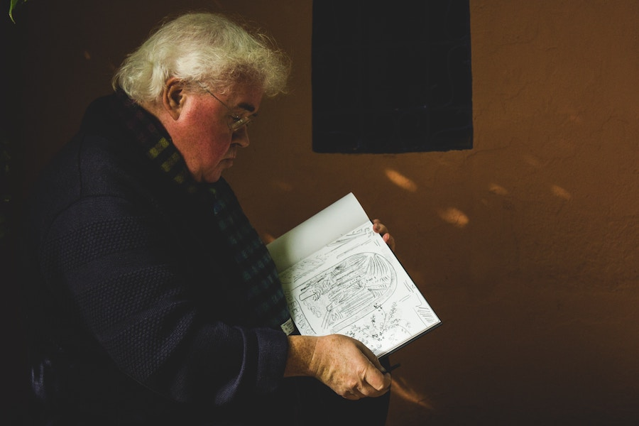 senior man reading in room